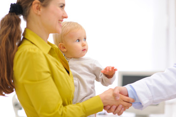 Closeup on mother with baby thanking pediatrician doctor