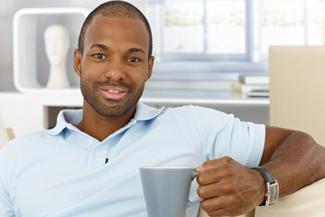Cheerful man at home having tea