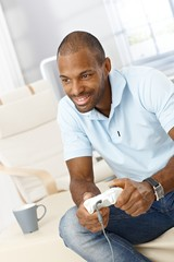 Smiling man playing computer game