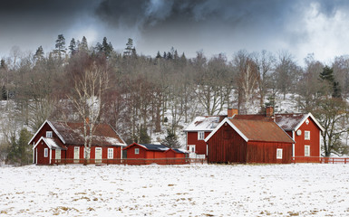 small farm in winter, storm clouds approaching