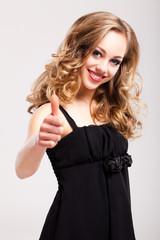 junge blonde Frau zeigt Top-Daumen