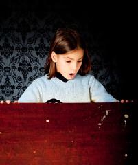 little girl looking inside a trunk