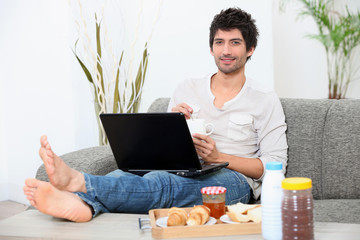 man doing computer and eating breakfast on sofa