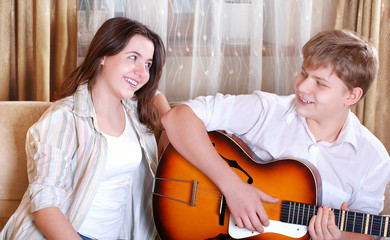 Two teenagers - boy and girl singing together by guitar