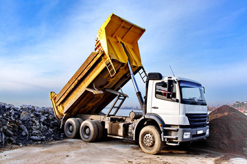 Dump truck is dumping gravel on an excavation site