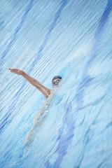 Swimmer in goggles, cap swimming back crawl