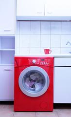 Rote Waschmaschine in weißer Küche