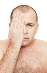 Naked man covering his eye