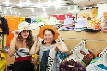 women  chooses hat at  shop