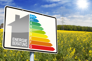 Ortseingangsschild mit Rapsfeld und Energieberatung