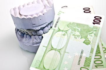 Zahnprothese Kosten Gebiss beißt auf Geldscheine