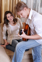 Teenage boy playing on guitar for his girlfriend