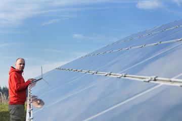 engineer using laptop at solar panels plant field