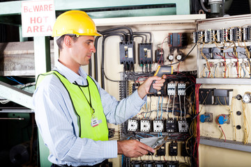 electrician checking industrial machine control box temperature