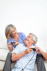 Lachende Senioren spielen Videospiel