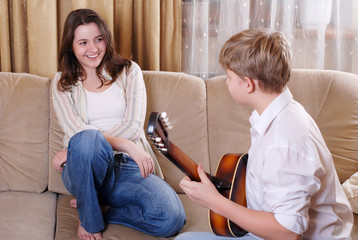Teenage boy playing on guitar for his girlfriend 1