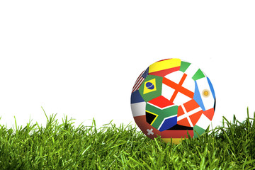 Classic soccer ball with flags  on green grass isolated on white