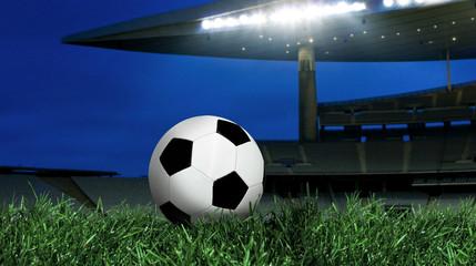 Soccer ball on green grass and illuminated stadium at night