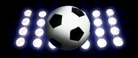 Soccer ball and spotlights at night