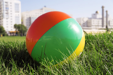 ball for outdoor games lying on grass in city park
