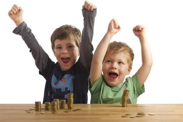 Zwei jubelnde Jungs vor Geldstapeln