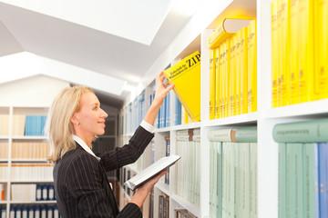 Business Frau steht am Bücherregal