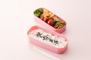 ピンクのお弁当箱とピンクの背景