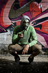 Man wearing gas mask in alley with grafitti background