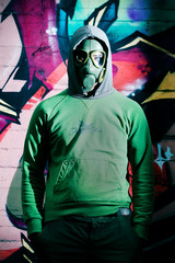 Man in front of graffiti with the gas mask on his face