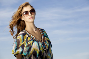 beautiful girl in sunglasses on background blue sky