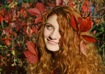 Portrait of a beautiful young girl with leaves in hair