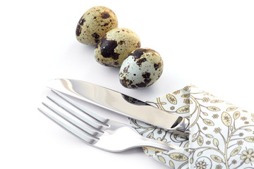 Knife and fork in a napkin with quail eggs.