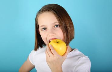 Girl eating a yellow apple
