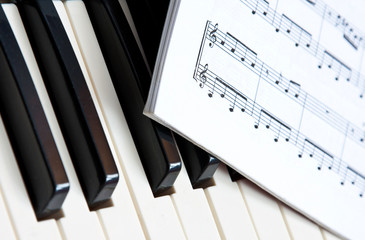 A music book lying on the keys of a piano