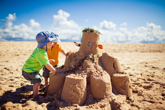 Two boys building large sandcastle on the beach