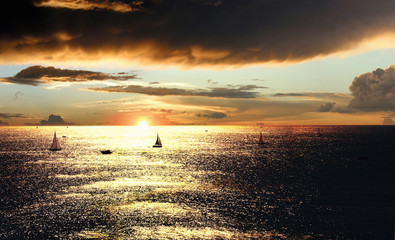 Dramatic sunset over the sea with sailing boats