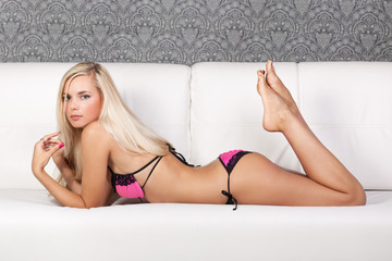 Portrait of a young beautiful blond girl in pink underwear