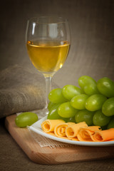 A glass of white wine, green grapes of wine on a wooden surface