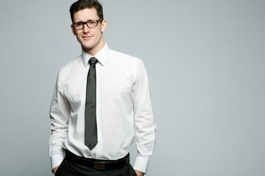 Handsome businessman in white shirt on gray background.