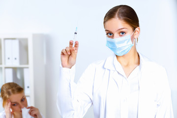 Nurse with syringe doing vaccination in office