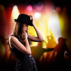 brünette Frau in Partyoutfit mit Hut