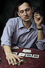 young man with cigar playing poker.