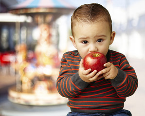 portrait of a handsome kid sucking a red apple against a carouse