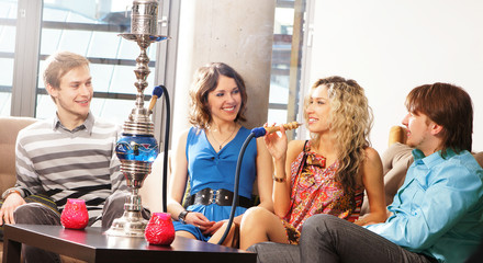 A company relaxing in a restaurant and smoking a hookah