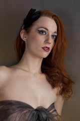 Redhead girl in a dress of black transparent fabric