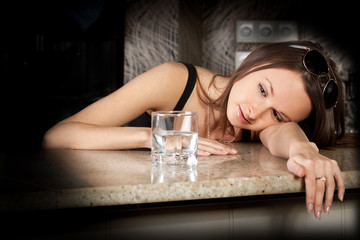 Drunk young girl with a glass of vodka