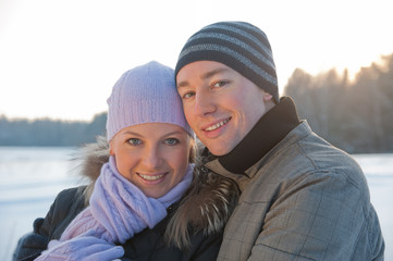 Smiling man and woman at sunlight on the winter background