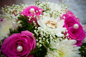 Wedding rings on a wedding bouquet.