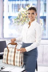 Beautiful businesswoman packing in office smiling
