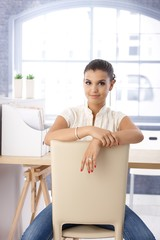 Attractive girl sitting conversely on chair